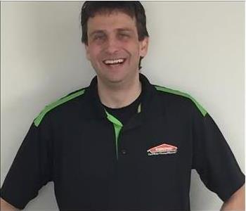 Male employee with black hair and shirt smiling for staff picture.